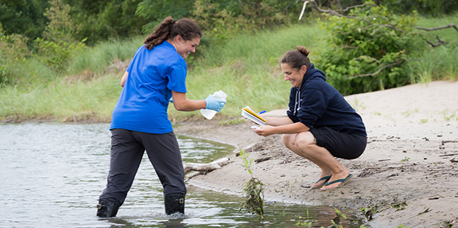 two students taking samples from a river